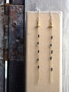 Black and golden beads intertwined on a gold filled chain create a long sassy pair of dangling earnings. The length and delicacy of this pair create