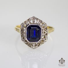 Period: Art deco (1920-1935) Composition: 18K gold and Platinum Stones: - 6 Rose cut diamonds of J-SI1 quality that weigh 0.06ctw. - 1 synthetic square cut sapphire that weighs 2ctw. Ring size: 6 Ring