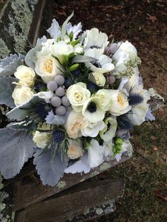 White garden roses, anemones, freesia with silver brunia, dusty miller and blue thistle put a twist on a classic.