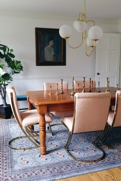 Hollywood inspired dining room // amazing white globe light fixture, white walls, pink and gold chairs, wooden table, blue rug