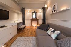 Un salon en longueur avec canapé gris cosy, et meuble sur mesure pour accueillir le bureau.