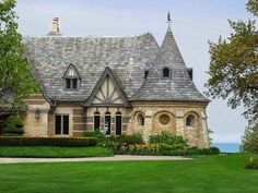"""This French Normandy style cottage is distinguished by a round stone tower with a conical roof. Also note the """"sag"""" or """"crook"""" in the slate stone roof -- a construction detail often employed in American cottage style homes to help give them an age-old appearance."""