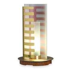 This is an object that is intended primarily as a landmark. It is not static, rather playful, interesting as open as closed. In the landscape of an interior, it is a lamp; rather an architecture that lets handle and can also make the Light. Polished brass and brushed  base walnut high gloss  shade sandblasted glass gradient