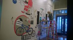 THE Studio artist Natasha Marie working on original hand-painted wall mural at Via 6 Seattle