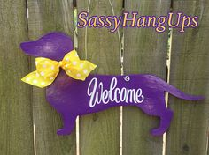 LSU Dachshund Door Hanger, LSU Tigers, Dog Door Hanger, Dog Door Decoration, Dachshund, Welcome Sign, Weenie Dog Hanger, Dachshund Gift, When you love your weenie dog and the LSU tigers!  Birch wood measures approximately 24 x 13 x 1/4. Painted purple on both sides for that finished look and sealed both sides for protection. Welcome wording painted white  A wire hanger is attached for easy hanging.  Yellow polka dot ribbon  Please favorite this item and my shop to receive all my new desi...