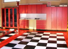 Bright red cabinets and black/white checker floor in a Branson, MO garage - by Garage Designs of St. Louis