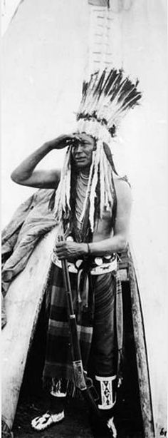 Standing portrait of a Native American Flathead (Salish) man, identified as Loma Joscum. He stands in the entryway of a tepee shielding his eyes with his right hand. In his left hand he holds a rifle. He wears moccasins, leggings, a breech cloth, a decorative beaded belt, necklaces, and a headdress with feathers and strips of fur. Date 1907