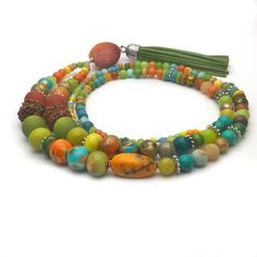 Celebrate life with this brightly coloured long boho pendant necklace! Lovingly handcrafted with a wide selection of gemstones like crackled agate, imperial jasper, candy jade and reconstituted turquoise Interspersed with hand painted wooden beads, silver coloured metal spacers and natural rudraksha prayer beads. The finishing touch is a natural sponge coral heart and a faux leather tassel. Length overall : 23.6 (60cm) UK customers please note: Your purchase is handmade in and posted from…