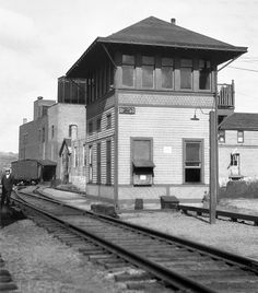 New Haven Railroad SS # B-253, NYNH&H Signal Station (Tower) is seen at Derby Junction, Connecticut, October 25, 1925. The unknown photographer caught an onlooker in the scene peering back at the camera. An old wooden ice activated refrigerator car is seen in the background located by what appears to be a refrigerated warehouse, because of the cooling tower located on top of the building. This Signal Station is located on the Naugatuck Line.