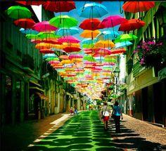 A pequena cidade de Águeda, em Portugal, decorou algumas de suas ruas com guarda-chuvas coloridos pendurados por fios de nylon 5 metros acima do chão. A impressão é que eles flutuam no ar, brincando com a imaginação de quem aproveita a folia desta festa urbana com referências circenses.