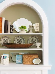 Simple Nooks  this arched display nook would be very easy to create!   Enhance by using contrasting paint colors.  Also: lighten the interior space of a deep bookcase by wrapping a few dark books in white or softly colored vellum covers. Layer small mirrors for extra sparkle. Or put pretty contact paper, vintage fabric, and even glue up those old square mirrors people used to use for walls.