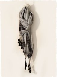 The shibori-dyed grey viscose scarf is bordered in lace ribbon and tipped with black tassels at the corners.
