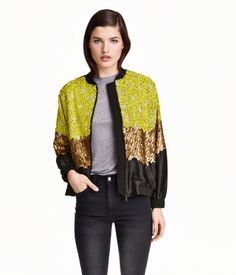 Short, boxy pilot jacket embroidered with beads, sequins and glittery thread at front and on sleeves. Front section and sleeves in woven satin fabric. Back, collar and ribbing in matte woven fabric. Zip at front, side pockets, and elastication at cuffs and hem. Lined.