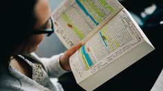 A young woman reads a heavily annotated book.