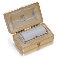 A Fabergé gold-mounted enamel cigarette case, workmaster August Hollming, St Petersburg, 1899-1904, oval section, the surface of translucent bluish white enamel over wavy engine-turning, the ends wrapped with chased leaf bands, the thumbpiece set with a cabochon ruby within rose-cut diamonds.
