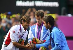 Gold medallist Andy Murray of Britain looks on as silver medallist Roger Federer of Switzerland (L) shakes hands with bronze medalist Juan Martin del Potro of Argentina during the presentation ceremony following the men's singles tennis gold medal match at the All England Lawn Tennis Club during the London 2012 Olympic Games August 5, 2012