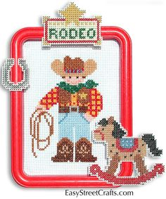 "RODEO COWBOY --57CB -- The rocking horse is just right for this little cowboy. He is stitched and framed in a red 5""x 7"" Hoop-Frame, on 11-ct Aida cloth. All materials are included plus 10-ct plastic canvas for stitching and decorating the frame. EasyStreetCrafts.com"