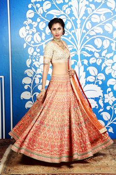 This Lehenga is master piece with a glimpse of Rajasthani culture and dori work .Here is a striking orange lehenga with gota embellishments and a classic gold raw silk choli with gota patti embroidery. An elegant orange net embroidered dupatta completes the look. A pretty lehenga set which showcases tradition with an endearing modern allure.