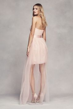 This short tulle bridesmaid dress features a long sheer overlay set off by a…