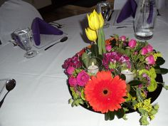 Dish garden centerpiece with yellow tulips, dianthus, gerbera daisies, kermits, solidago, spray roses, and completed with candles