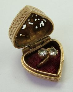 A 1960s English 9ct gold heart shaped ring box charm that opens to reveal a clear gem set crossover engagement ring inside, hallmarked for 1965.