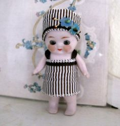 This is a precious little German doll from the 1920s. This dolls outfit will be made to order. I no longer have the exact flowers for her hat but will attach similar ones. Allow 8 business days for shipment. She has big black birdlike eyes. Shes in excellent condition. Shes wearing a little hat/bonnet adorned with forget-me-not millinery, and underneath that is an open pate. Her arms are jointed and her legs are straight. Her eyes are glass and they stay open because they lost their we...