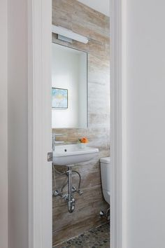 cottage powder room with plank walls features a wall mount sink above the river rock floor
