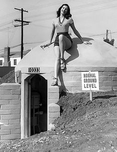 Fearless lady posing on a bomb shelter in 1950. Support strong women by shopping the Women's Causes section in the shop!