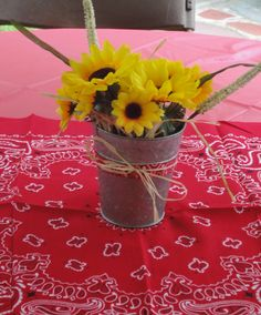 A western party centerpiece using tin cans, raffia to fill and artificial flowers. I used bandanas as a center runner.
