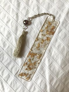 Clear bookmark made using resin - features glitter and gold flake accents with a tassel and sparkling beads. #art #artist #abstract #resin #bookmark #resinbookmark #reading #books #hamsahand #handmade #etsy #etsyshop #etsyseller #forsale Diy Resin Art, Diy Resin Crafts, Diy Crafts Videos, Diy Crafts To Sell, Resin Jewlery, How To Make Bookmarks, Corner Bookmarks, Bead Art, Cute Jewelry