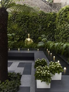 Dering Hall. Terrace with gray stone tiles, gold Buddha, square white planters, ivy walls and lighted water feature.