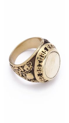 Mania Mania Astral Plane Signet Ring  Mania Mania puts an edgy, antiqued spin on an old-school classic. This polished, faceless signet ring has tiny skulls carved into the sides, while abstract 'Meet Me At The Astral Plane' lettering is tooled into the setting.  Brass.  194.09 CAD