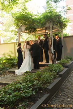 The bride's father and mother walked her down the aisle and up to the pergola to her groom.