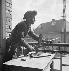 Private H.K. Keller of the South Saskatchewan Regiment, who is armed with a Bren gun, on the second floor of a building in Nieuwpoort. September 9, 1944.