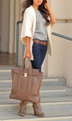 Outifit de otoño, Chaqueta de punto, camiseta gris, vaqueros con cinturón, botines de tacón marrón del mismo color que su bolso.