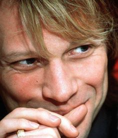 Jon Bon Jovi sporting a sexy, mischevious smile and his wedding ring