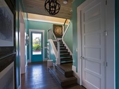 A first glimpse of the home's sea-inspired color palette and High Regency design focus, the foyer celebrates Jacksonville Beach history and showcases locally sourced building materials.
