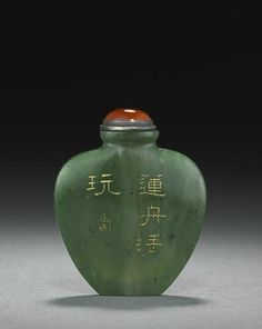 An inscribed spinach jade snuff bottle. Probably Imperial, Palace Workshops, Beijing. 1770-1800.  Of flattened, high-shouldered ovoid form with a short neck, flat lip and foot, one side neatly incised with an inscription reading 'Lianzhou qingwan' (for refined enjoyment of Lianzhou), followed with a small cartouche, all heightened in gilt wash; the grass-green stone cast with lighter and dark gray inclusions. 2 1/4in (5.7cm) high