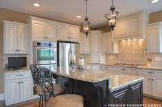 Glazed white cabinets, dark island, travertine backsplash, lantern lighting, tan walls