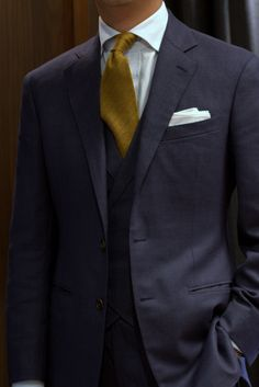 Navy suit, white shirt with blue pattern, gold tie