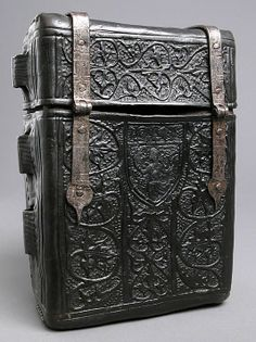 Case for a Book (the original messenger bag)   Leather (Cuir bouilli) and metal mounts. On the back is an unidentified coats of arms with a crozier and mitre, suggesting that this protective cover for a book belonged to a bishop.