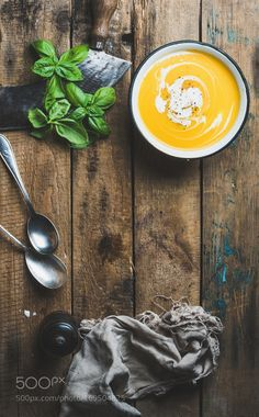 Pumpkin cream soup in bowl with fresh basil and spices by 2enroute