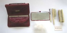 "Small French Fashion doll accessory antique red soft leather Necessaire, has a locking clasp on the outside.  4"" x 2"" includes 2 celluloid brushes, button hook, puff & mirror  425.00"
