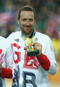 Gold medalist Bradley Wiggins of Team Great Britain poses for photographs after…