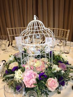 Decorative Ivory Birdcage filled with fresh rose petals and surrounded by a summer circlet of Peonies, Lavender Roses, and Freesias