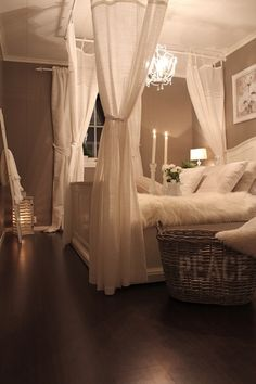 A Romantic master bedroom... love the idea of hanging the curtain rods from the ceiling... makes the bed such a cozy getaway for two :) love the chandelier