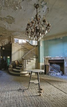 An elegant chandelier hangs from a peeling ceiling in this abandoned mansion somewhere in New Jersey. Source: jgurbisz (flickr)
