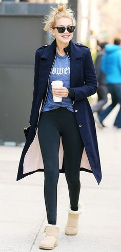Gigi Hadid pairs a navy coat with a graphic t-shirt, leggings and Ugg mini boots.