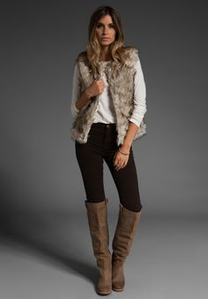 Fur vest, black skinny jeans & over-the-knee boots, but somehow doesn't look like a hooker