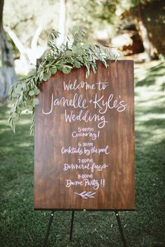white script on wooden board accented with greenery for wedding schedule of…